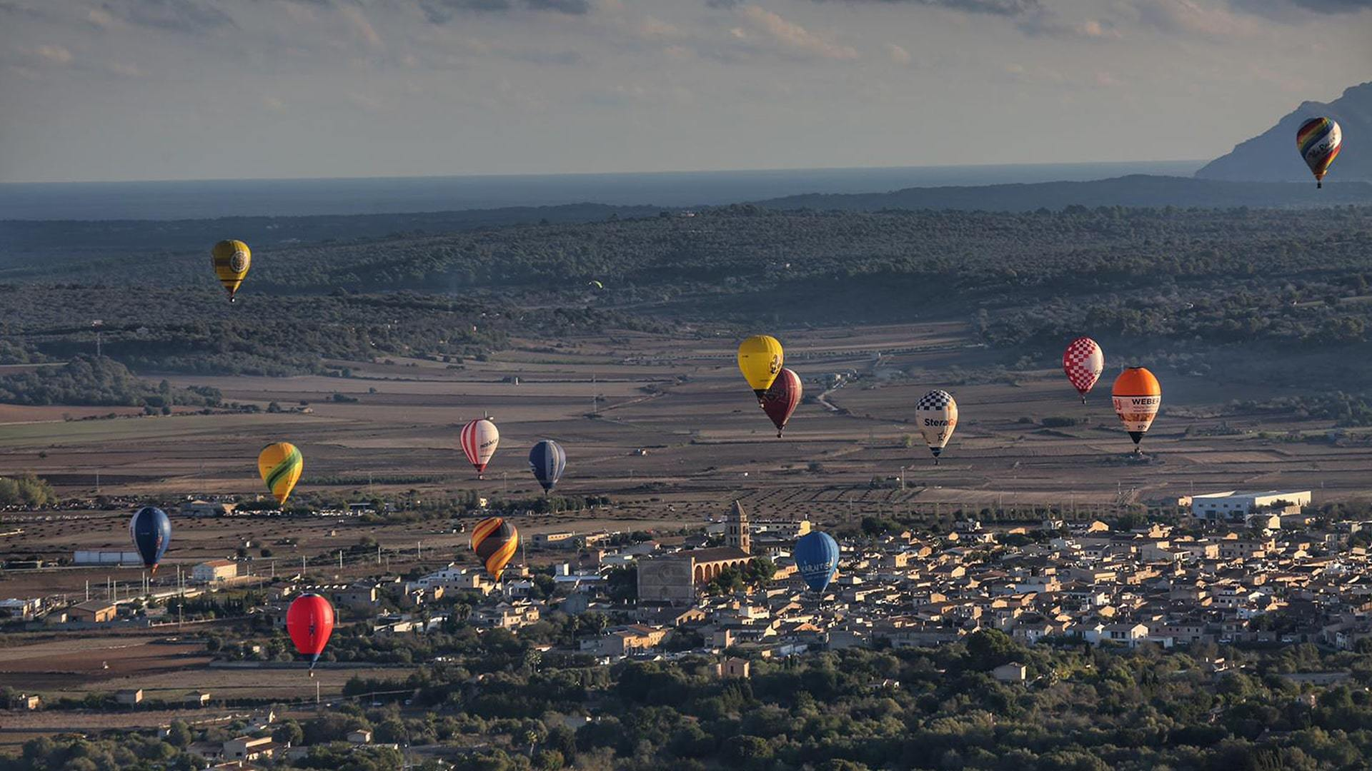 Hot air balloons flying over Manacor town Mallorca incredible spectacular view min